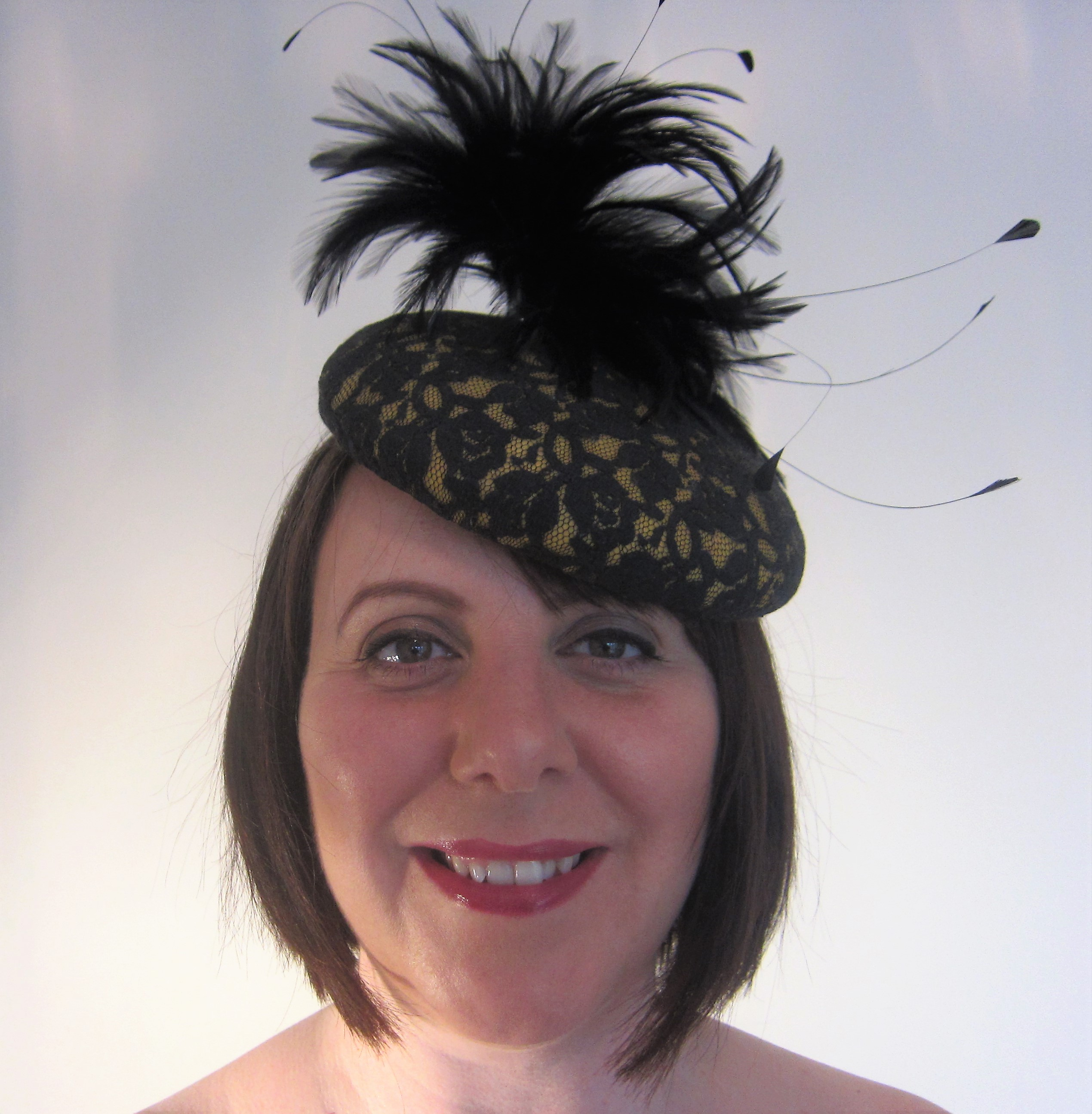 Yellow felt button with black lace and attractive black feather mount.